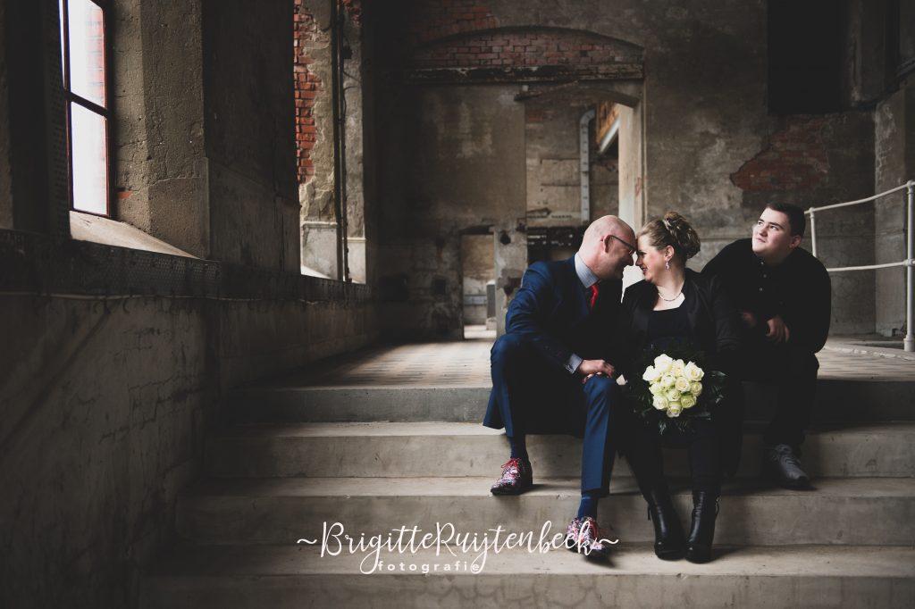 Bruidsfotografie van man, vrouw en jongen op trap in oude fabriekshal.