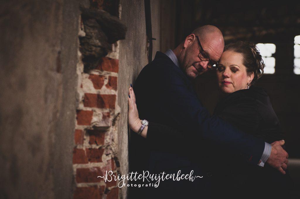 bruidsfotografie van bruidegom en bruid in innige omhelzing met ogen dicht.