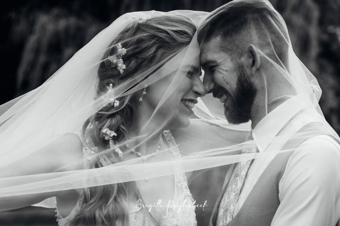 Bruidspaar onder bruidssluier in zwart wit