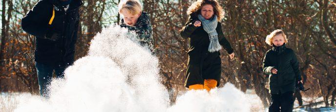 Gezin rent door de sneeuw