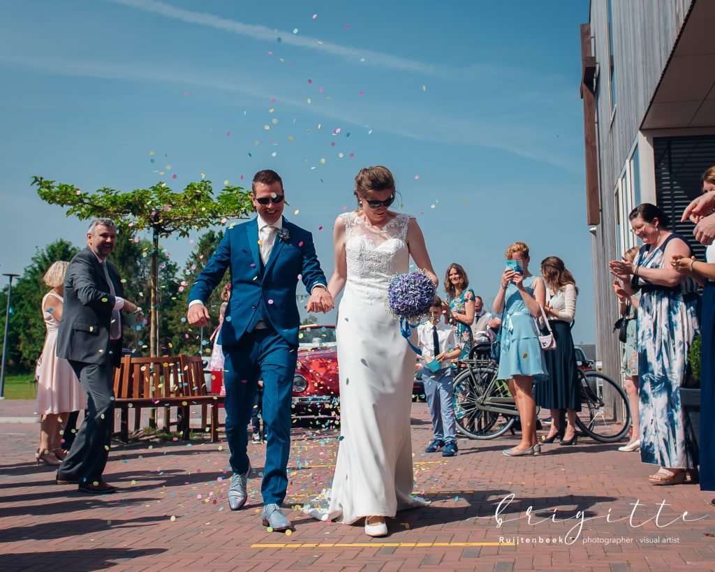 Bruidspaar met zonnebrillen en confetti